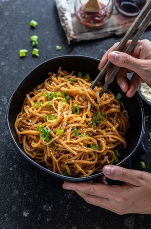 pair of hands holding a bowl of noodles with one hand holding a pair of chopsticks