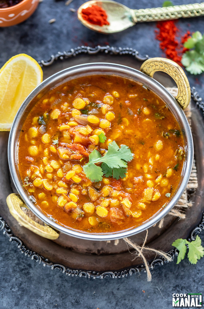 chana dal served in a copper kadai and garnished with cilantro