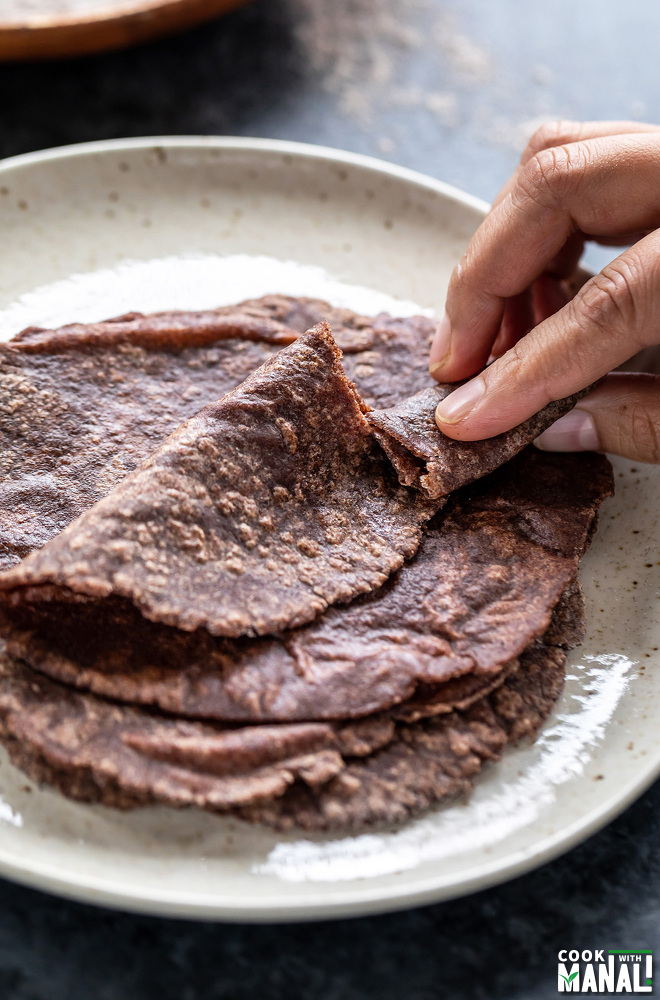a hand breaking off a portion of the ragi roti