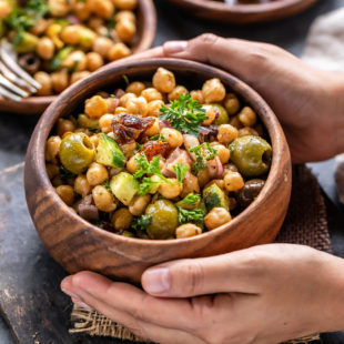 pair of hand holding a bowl of chickpea salad served in a wooden bowl
