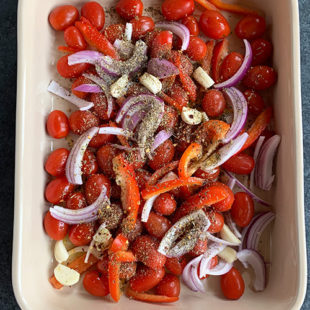 baking dish with cherry tomatoes, onions, spices