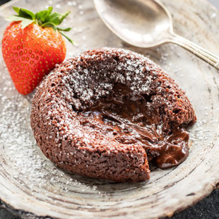 chocolate lava cake placed on a plate with melted chocolate oozing from the center