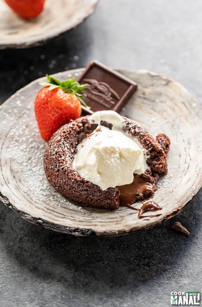 eggless chocolate lava cake served on a plate topped with ice cream and a strawberry and chocolate piece placed on the side