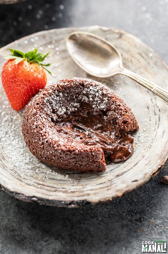 chocolate lava cake placed on a plate with molten chocolate flowing through the center and a strawberry placed in the back