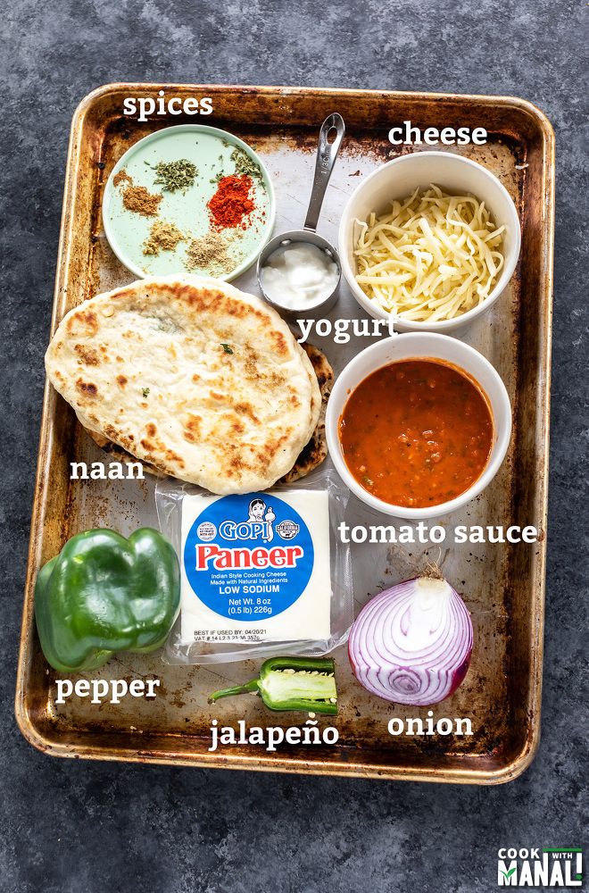 ingredients of paneer tikka naan pizza arranged on a baking tray