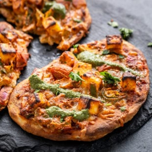 Naan Pizza placed on a black round board and drizzled with chutney