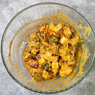 paneer, onion and peppers coated with a marinade in a bowl