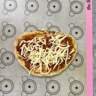 a naan with tomato sauce and cheese applied on it