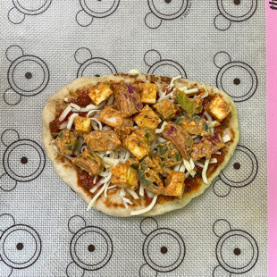 cubes of paneer and veggies on top of a naan
