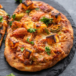 baked naan pizza placed on a black board
