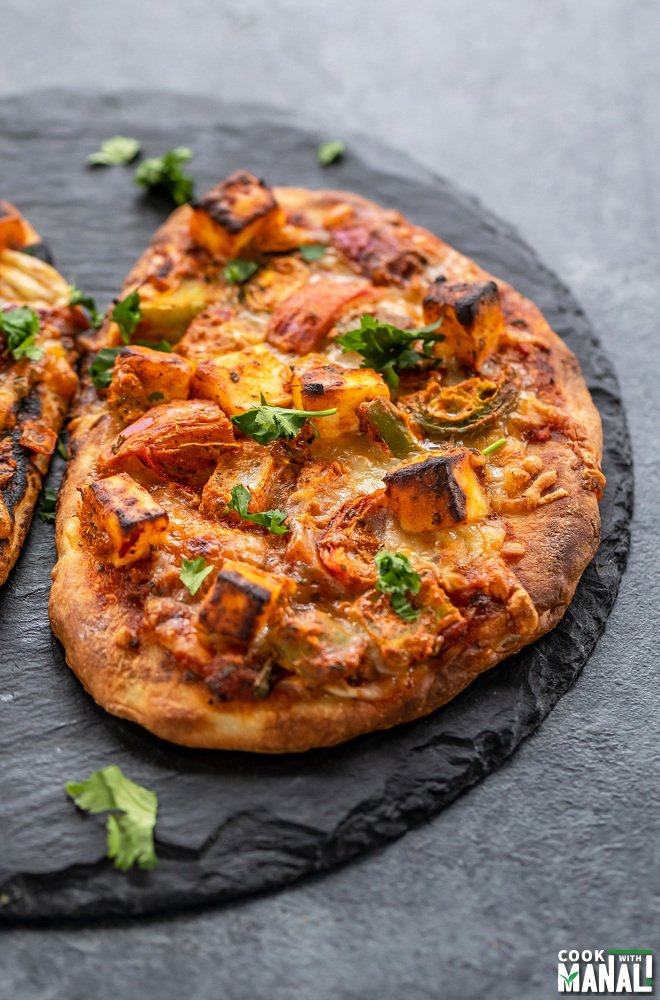paneer tikka naan pizza placed on a black board