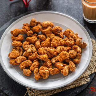 spice coated cashews on a plate with glass of chai on the side and also in the back