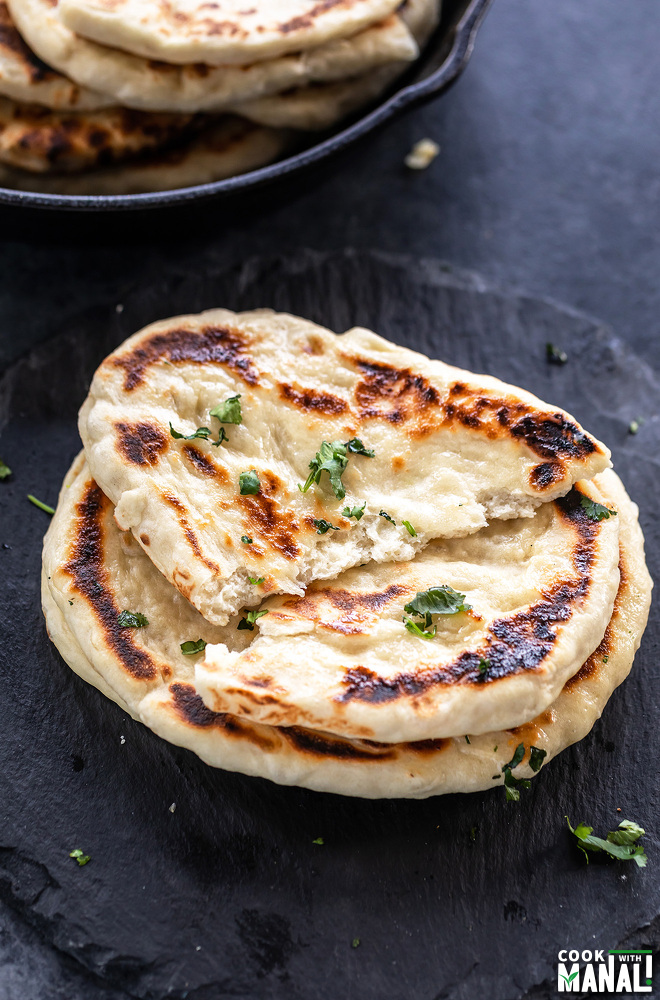 a naan torn apart into two to show the texture of the naan
