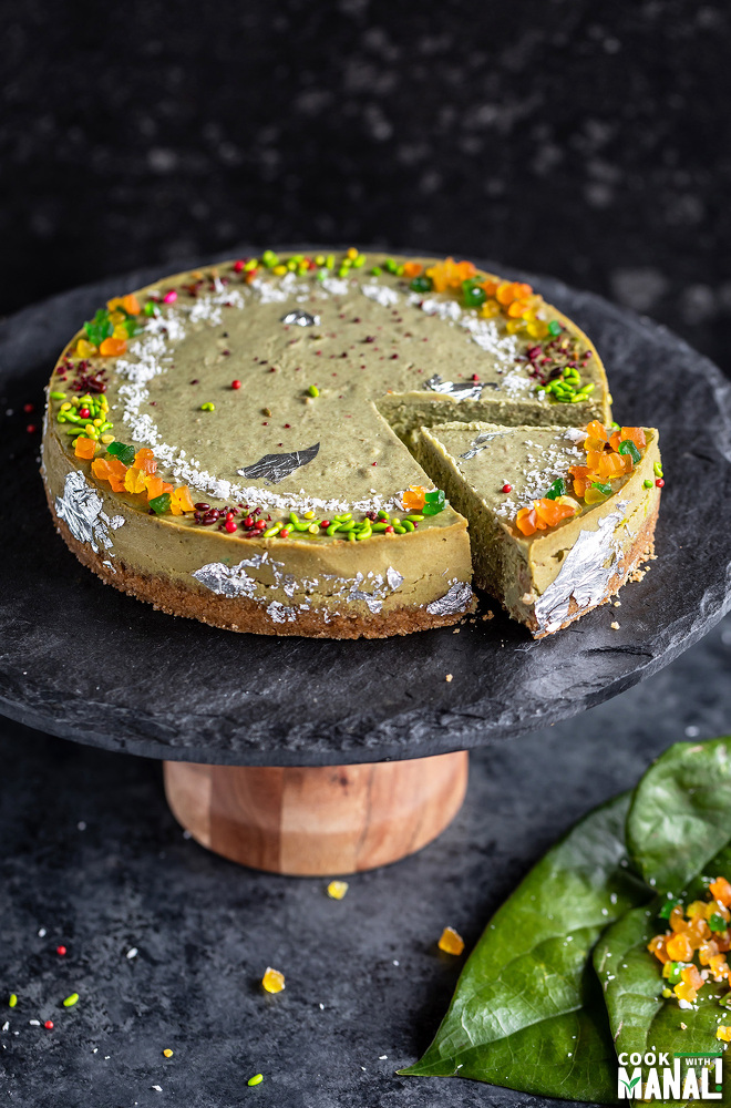 paan cheesecake served on a black stand with few paan leaves on the side