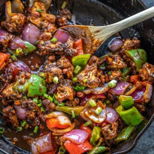 cast iron skillet with cauliflower, onions and peppers tossed in a sauce