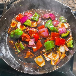 onions, peppers tossed in a sauce in a skillet