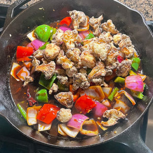 air fried cauliflower being added to a skillet with onions, pepper and sauce