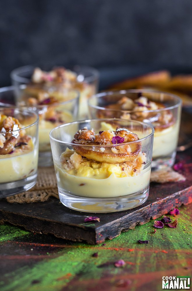 small dessert glasses filled with rabdi, malpua and garnished with dried rose petals