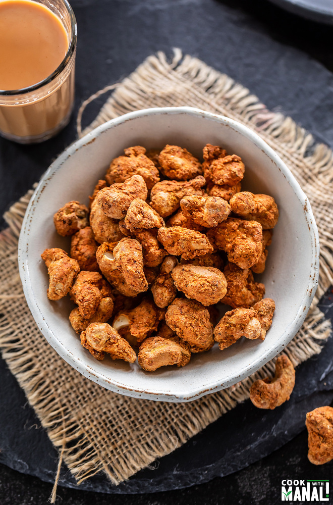spicy cashews placed in a bowl with a glass of chai on the side