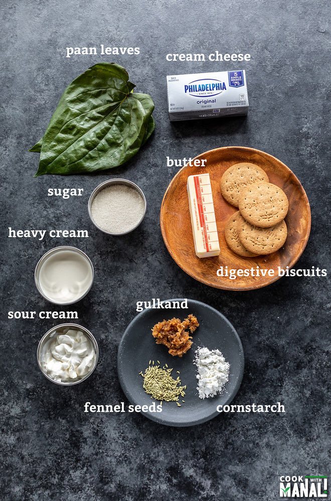 bowl of sugar, cream, sour cream, some paan leaves, biscuits all arranged on a board
