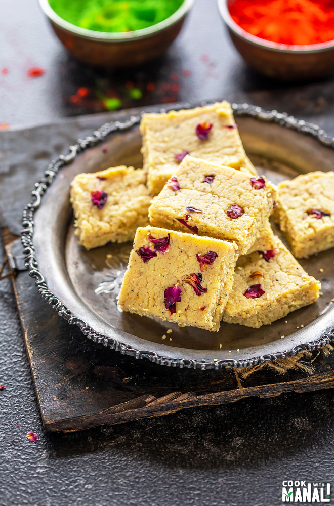 plate of thandai burfi with holi colors in the background