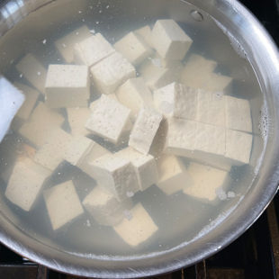tofu submerged in hot water in a pan