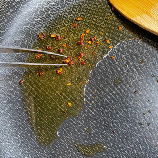 sichuan peppercorns in oil being picked by tweezer