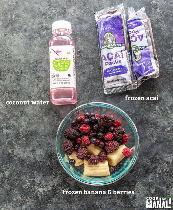 bowl with frozen fruit, bottle of coconut water and packs of frozen acai laid down on a board