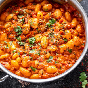 gnocchi in tomato sauce in a steel pan garnished with cilantro