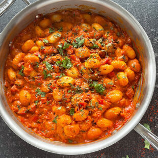 gnocchi is tomato sauce served in a pan and garnished with cilantro