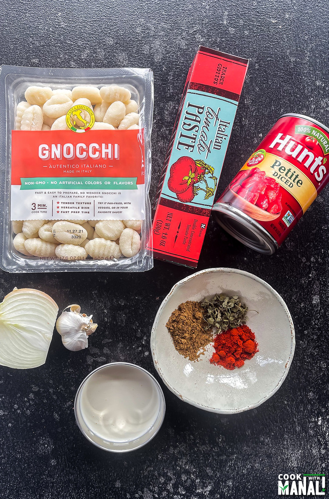 packet of gnocchi, tube of tomato paste, can of diced tomatoes, spices placed on a board