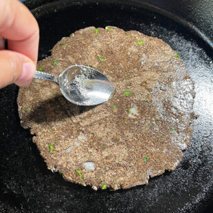 oil being applied to a flatbread on a skillet