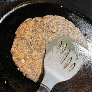 spatula pressing a buckwheat flour flatbread being cooked on a skillet