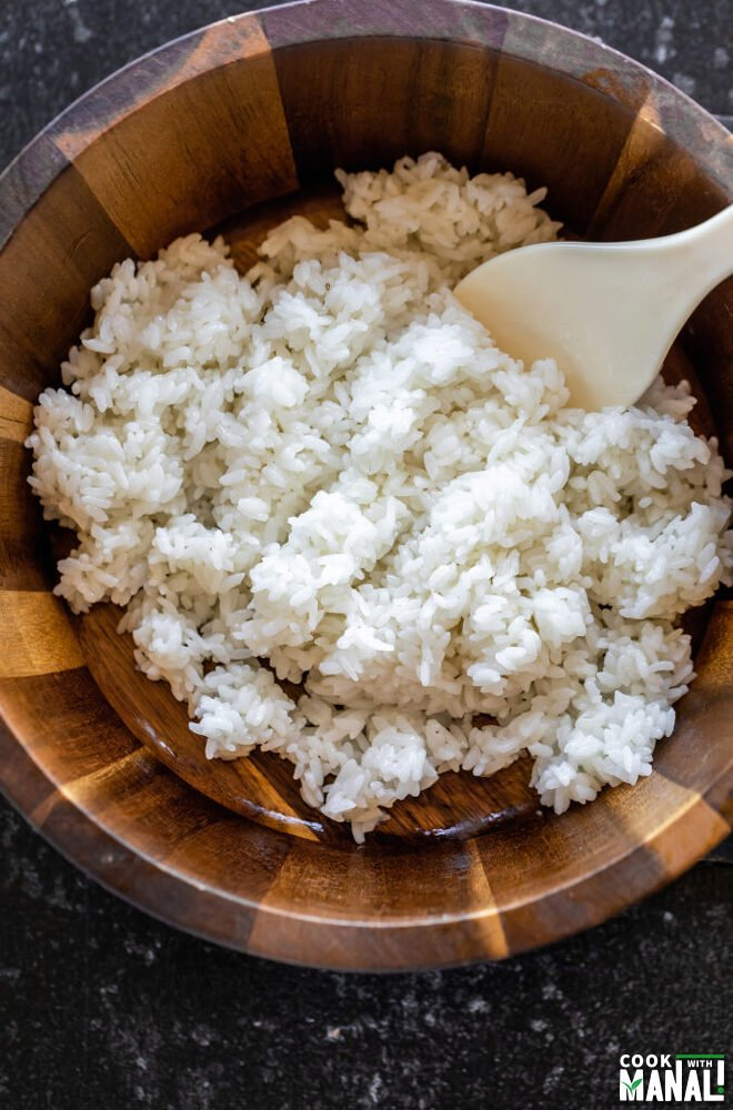 white rice in a wooden bowl with a rice paddle