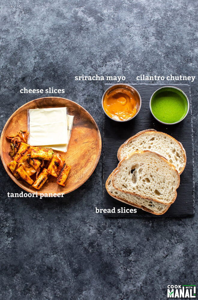 2 bread slices, a bowl of chutney, 2 cheese slices, paneer pieces all placed on a board