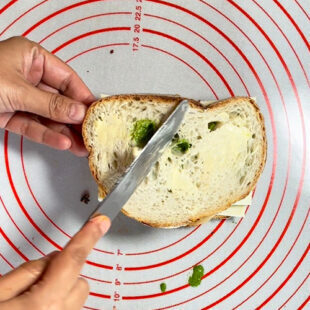 butter being applied with a butter knife on a bread