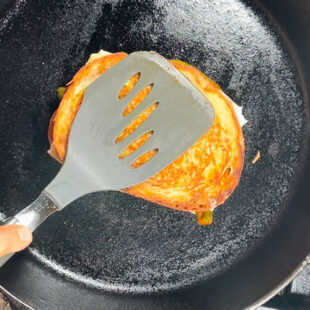 sandwich being pressed with a spatula on a pan