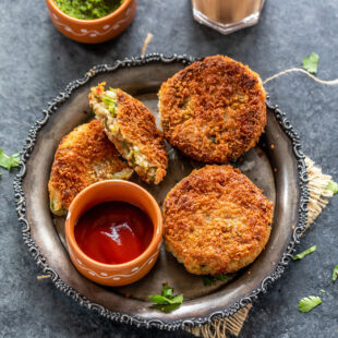 3 veg cutlet placed on a plate with a bowl of ketchup and bowl of chutney and glass of chai in the background