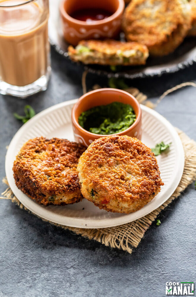 2 veg cutlet in a plate with bowl of cilantro chutney and glass of chai in the background
