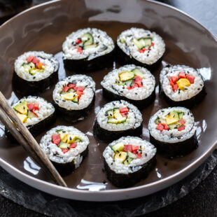maki rolls filed with cucumber, avocado, carrots placed in a bowl
