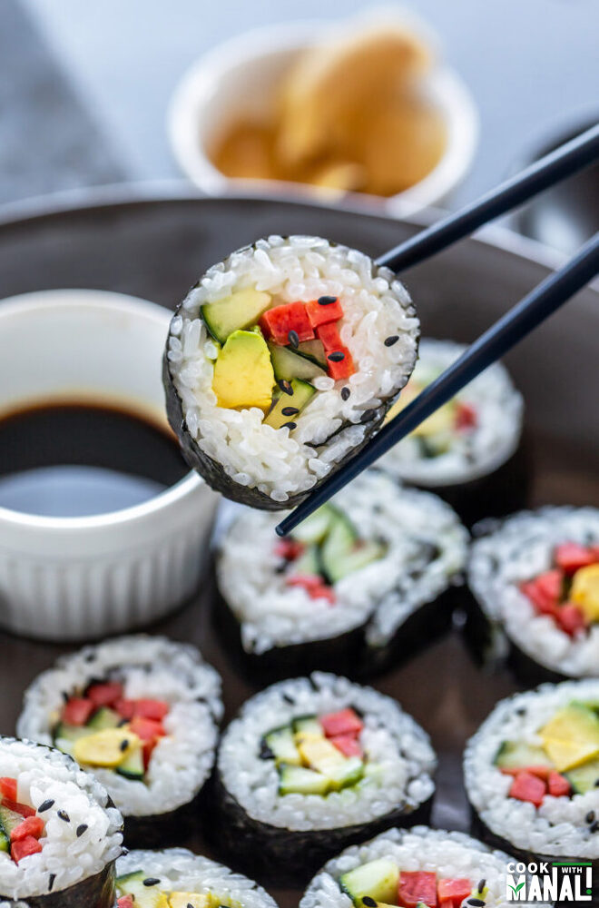 pair of chopstick holding a vegan sushi roll