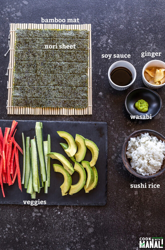 all ingredients for making vegan sushi like nori, bamboo mat, veggies laid down on a board