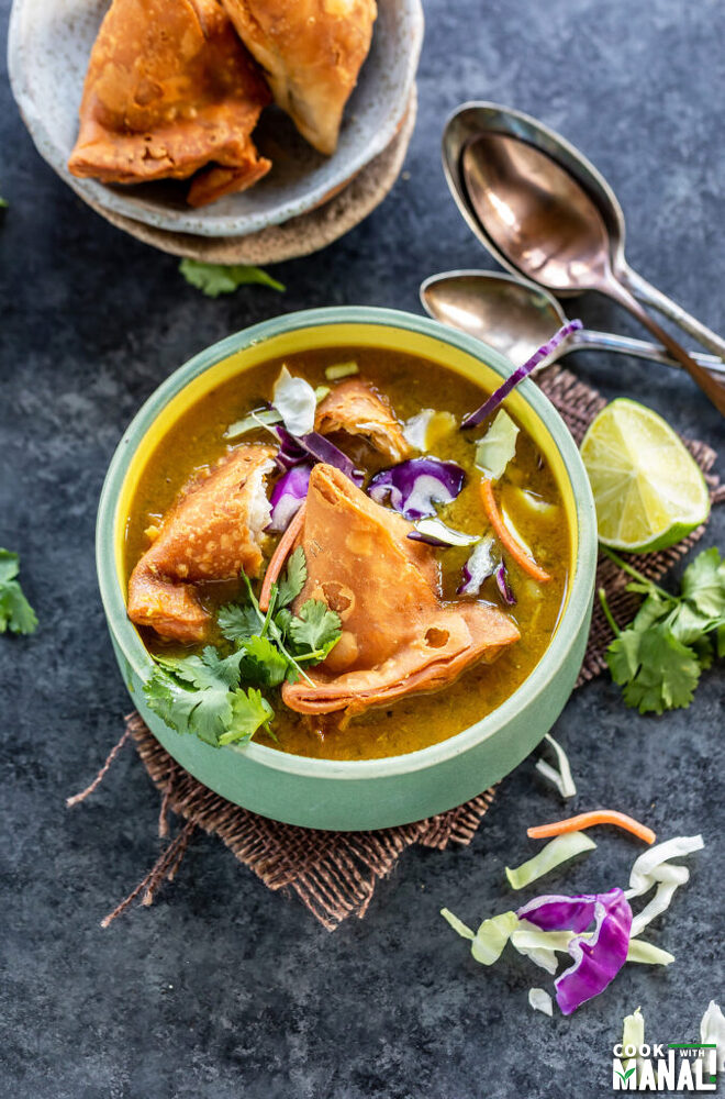 soup bowl topped with samosa, cilantro, sliced cabbage with lime wedge on the side