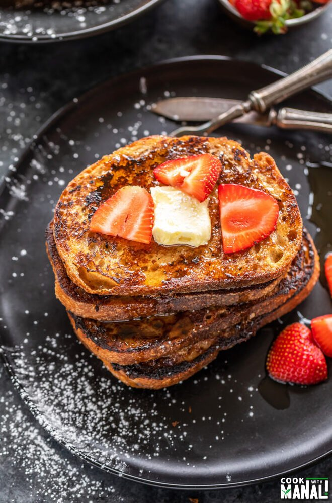 stack of French toast topped with butter and strawberries with bowl of strawberries in the background