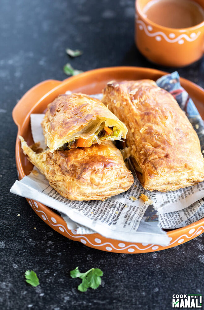 a veg puff cut into half to reveal the filling and a cup of chai placed in the background