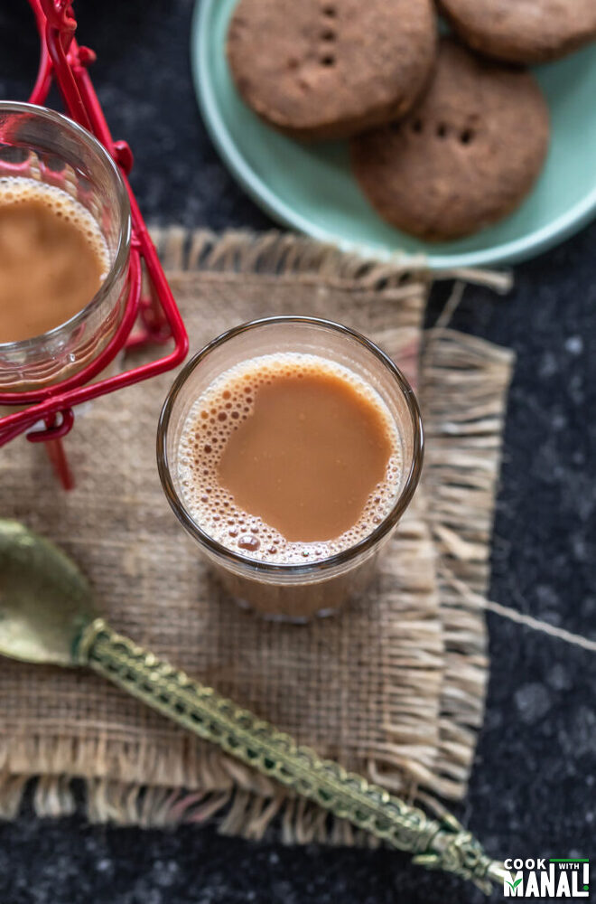 glass of chai with cookies placed on the side