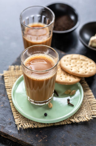 glass filled with chai and 2 cookies placed on the side