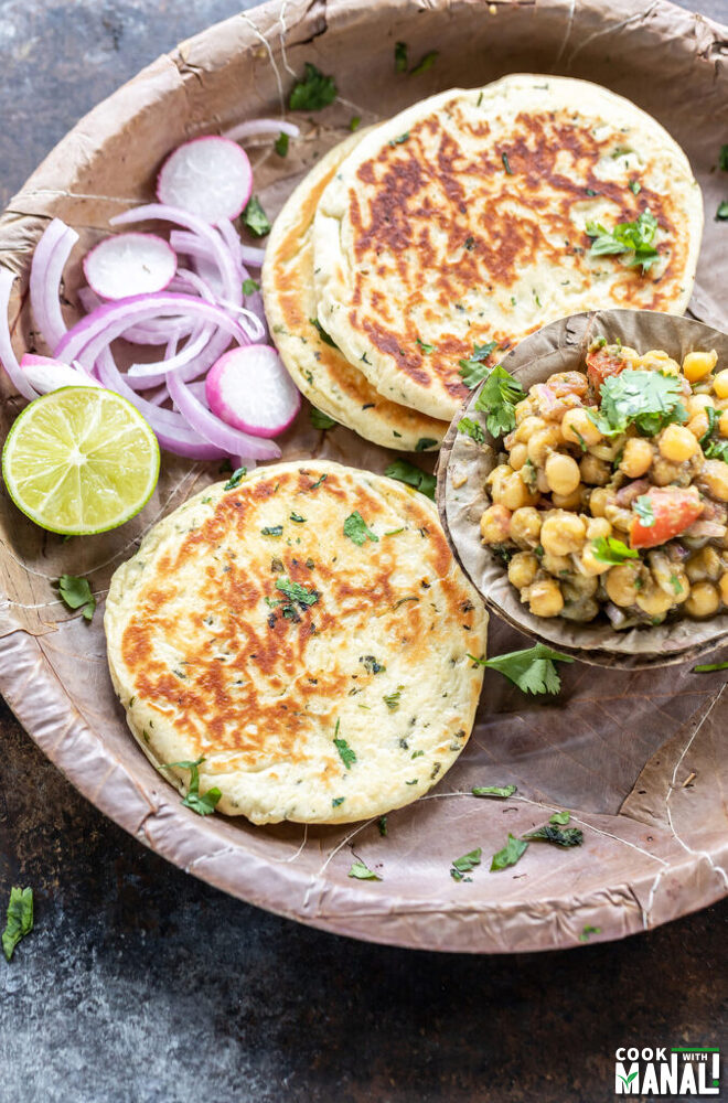 bread kulcha served with a bowl of matar chaat, sliced onion and a round of lemon in a pattal