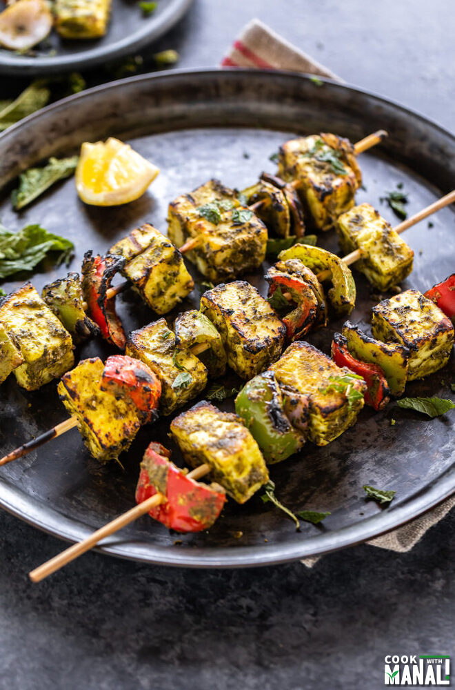 3 skewers of hariyali paneer tikka placed on a round plate with a lemon wedge on the side