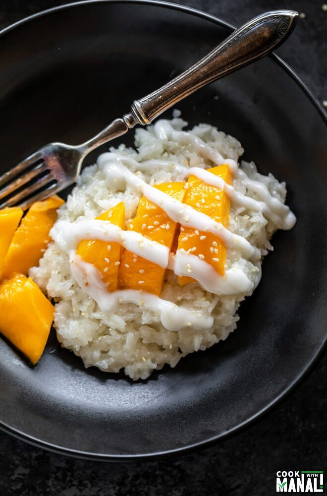 sticky rice drizzled with coconut sauce and topped with sesame seeds served with slices of mangoes